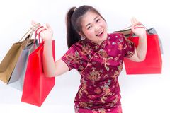 Young asian woman wearing chinese dress traditional cheongsam with Carrying a shopping bag and smile. Chinese New Year Royalty Free Stock Photography