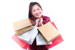 Young asian woman wearing chinese dress traditional cheongsam with Carrying a shopping bag and smile. Chinese New Year Festivities, New Year Celebration Royalty Free Stock Images