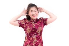Young asian woman wearing chinese dress traditional cheongsam with gesture of congratulation,. Looking at the camera and smile in Chinese New Year Festivities Royalty Free Stock Photography