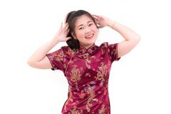 Young asian woman wearing chinese dress traditional cheongsam with gesture of congratulation,. Looking at the camera and smile in Chinese New Year Festivities Stock Photography