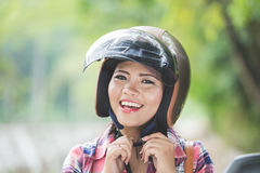 Young asian woman wearing a helmet before riding a motorcycle on Stock Images