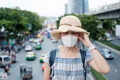 Healthcare and air pollution concept. Young Asian woman wearing N95 respiratory mask protect and filter pm2.5 particulate matter against traffic and dust city stock photography