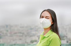 Young Asian woman wearing a protection mask against PM 2.5 air pollution in Bangkok city. Thailand. Reduce air pollution concept stock image