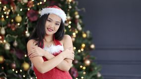 Young Asian woman wearing Santa Claus suit and hat smiling in background amazing Christmas tree. Seductive beautiful young Asian woman wearing Santa Claus suit