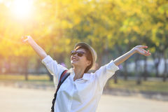 Young asian woman wearing white shirt and sun glasses rising han Stock Photography