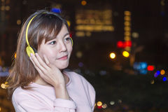 Young Asian woman wearing yellow headphones with c Royalty Free Stock Photo