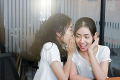 Young Asian woman whispering gossip in living room stock photo