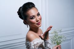 Young woman fashion portrait. Young asian woman in white dress with flowers air kiss posing portrait Royalty Free Stock Image