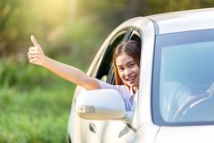 Young asian woman in white shirt driving her car and showing thumbs up stock photography