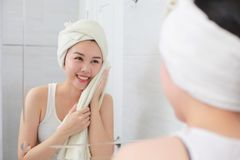 Young asian woman wiping her face with towel in bathroom royalty free stock photos