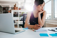 Young asian woman working at her desk. Shot of young asian woman working at her desk, writing notes. Businesswoman at her workplace Stock Photo