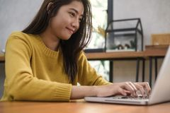 Young asian woman working with the laptop on a desk with her smile. Young woman working on weekend with her laptop in a warm sunlight day. Laptop working in royalty free stock image