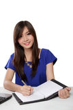 Young Asian woman writing on notebook on a table, isolated on white Stock Images