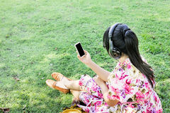Young Asian women back or rare view listen to music via headphon Royalty Free Stock Photo