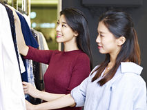 Young asian women in clothing store. Beautiful young asian women looking at apparels in a clothing store Stock Photos