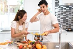 Young asian woman cutting slice vegetables making salad healthy food. Young asian women cutting slice vegetables making salad healthy food with fruits and men Stock Images