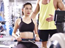 Young asian adult woman exercising using rowing machine Royalty Free Stock Images