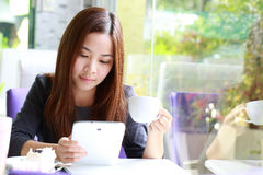 Young Asian women holding a cup of coffee beside mirror Stock Photo