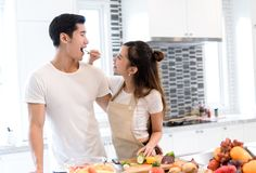 Young asian woman holding vegetables to man eating each for cooking dinner. Young asian women holding vegetables to men eating each for cooking dinner healthy Stock Image