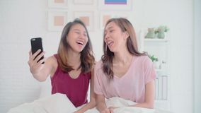 Young Asian women lesbian happy couple using phone VIDEO Call with friend in bedroom at home. stock footage