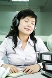 Young asian women listening music. During working ,have a break Royalty Free Stock Photos