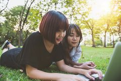 Young asian women lying on grass and using laptop and typing. Girls hands on keyboard. Royalty Free Stock Photo