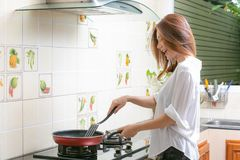 Young asian woman making omelette in a kitchen. royalty free stock photos