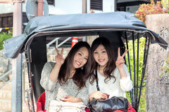 Young Asian women in rickshaw, Kyoto, Japan. Two beautiful, smiling women in a rickshaw (carriage) in Kyoto, Japan, give the peace or victory sign with their Royalty Free Stock Image