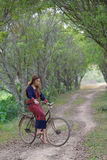 Young asian women sit on an old bike in rice field area. Stock Images