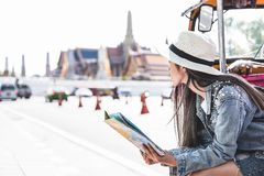 Young Asian women sitting in local taxi holing a map with Grand Palace as a blurred background, Bangkok Thailand. Young Asian woman sitting in local taxi holing stock photo
