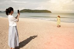 Young Asian woman standing and taking a photo on the beach. Young asian women standing on the beautiful nice blue beach with white sand and taking photo with Stock Photos