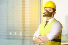 Young asian worker man in safety vest, gloves, yellow helmet and protective mask standing. In the office with skyscrapers background royalty free stock photography
