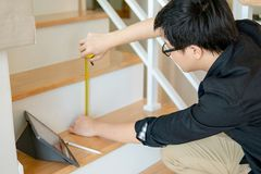 Asian worker using tape measure on ladder. Young Asian worker using tape measure for measuring riser and thread on stair in the house. Writing note and sketching Stock Photography