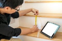 Asian worker using tape measure on ladder. Young Asian worker using tape measure for measuring riser and thread on stair in the house. Writing note and sketching Royalty Free Stock Images