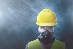 Young Asian Worker With Yellow Helmet And Protective Mask Stock Photo