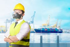Young asian worker with yellow hard hat, gloves and protective mask standing on the office royalty free stock photography