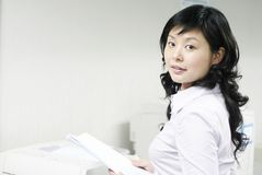 Young asian working with print. Young asian woman working with print in office Royalty Free Stock Image
