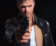 Young assasin pointing his gun to the camera Royalty Free Stock Photography