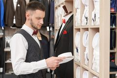 Bearded confident man choosing shirt in shop. stock photography
