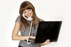 Young assistant doing multiple tasks at the same time. Talking on the phone and writing a text on her notebook. A typical moment from business life Stock Image