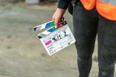 Assistant is holding a film flap in her hand. Young assistant holds the film flap in her hand for the next scene royalty free stock image