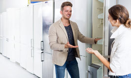 Young assistant in the shop sell a fridge stock photo