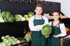 Young assistants demonstrating assortment. Young shopping assistants demonstrating assortment of grocery shop royalty free stock images