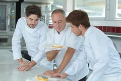 Young assistants and mature chef looking at finished cake. Chef royalty free stock photography