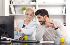 Young assistants working. Portrait of young financial assistants working together. Businesswoman and businessman sitting together and office in front of computer stock photos