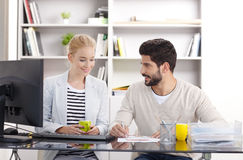 Young assistants working. Portrait of young financial assistants working together. Businesswoman and businessman sitting together and office in front of computer stock images
