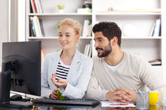 Young assistants working. Portrait of young financial assistants working together. Businesswoman and businessman sitting together and office in front of computer royalty free stock photography