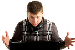 Young astonished businessman working on a laptop. White background Royalty Free Stock Photos