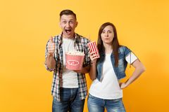 Young astonished couple woman and man watching movie film on date holding bucket of popcorn and plastic cup of soda or. Cola showing thumb up isolated on yellow royalty free stock images