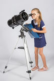 Young astronomer in glasses with interest peers into the eyepiece of the telescope. The young astronomer in glasses with interest peers into the eyepiece of the Royalty Free Stock Image